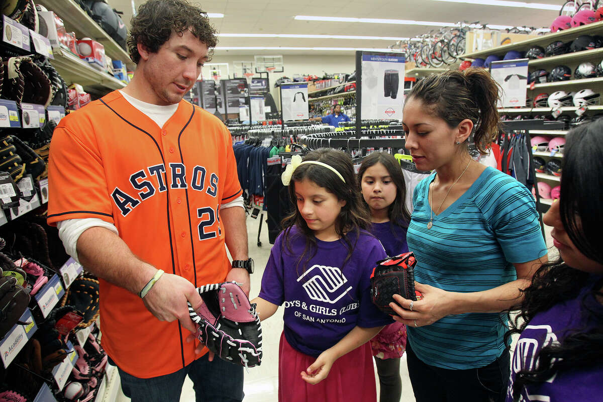 Houston Astros player Brett Wallace helps Ivory Serna select the proper glove while mom Dorothy Serna looks on with sister Shyanne (center) and Ebony - who are participants with the Boys and Girls Clubs shopping spree - before the Astros star signs autographs at the Academy Sports and Outdoors store at 1604 near Gold Canyon on Jan. 24, 2013.