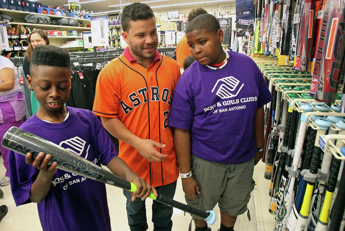 Houston Astros player Jose Altuve helps Boys and Girls Clubs shopping spree participants Rashad Henderson (left) and Corey Swan select a good at the Academy Sports and Outdoors store at 1604 near Gold Canyon in 2013.