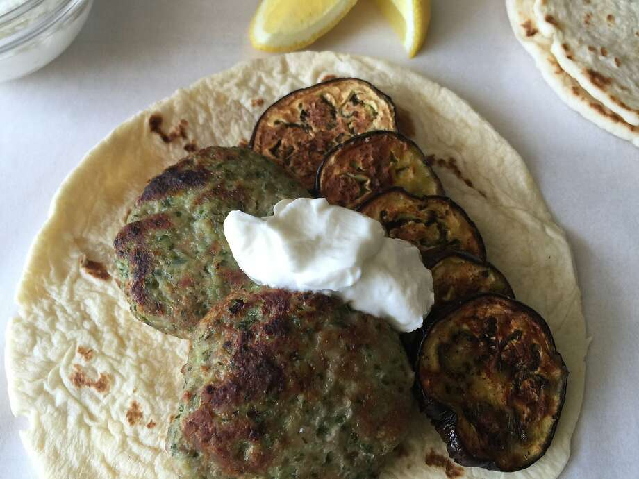 Chicken kofte are served with roasted eggplant, sliced lemons and yogurt. Photo: Amanda Gold