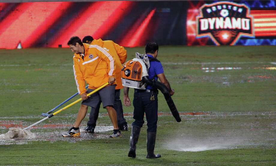 Workers uses squeegees and leaf blowers to remove water from the field before the Open Cup game at BBVA Compass Stadium between the Houston Dynamo and the Colorado Rapids Tuesday, June 30, 2015, in Houston.  ( James Nielsen / Houston Chronicle ) Photo: James Nielsen, Staff / © 2015  Houston Chronicle