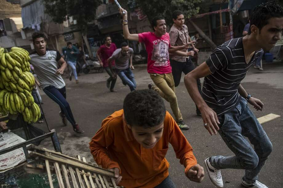 Supporters of the Muslim Brotherhood and bystanders run away from the Egyptian security forces during clashes following their protest on a street in Cairo's Matariya district, Egypt, Tuesday, June 30, 2015. Protesters were marching on a Cairo street Tuesday as authorities has declared the day a national holiday, two years after the mass protests that preceded the overthrow of President Mohammed Morsi. Photo: Belal Darder, Associated Press