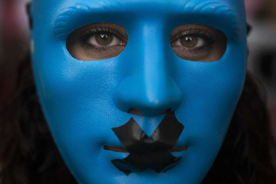 """A protester in Spain protests a """"gag law"""" in 2015. Photo: Andres Kudacki, Associated Press"""