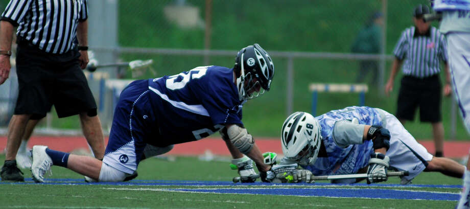 Staples' Ben Schwaeber, right, faces off with Wilton's RJ Romeo during a game in May. Schwaeber won 77 percent of the faceoffs he took this season for the Wreckers. Photo: / Ryan Lacey /Staff Photo / Westport News Contributed