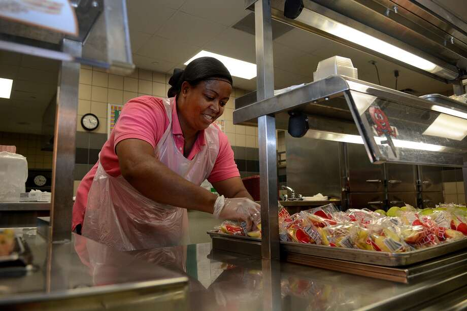 Marjorie McGinnis of Park Lakes Elementary School in Humble ISD, serves free lunches to students. Photo: Jerry Baker, Freelance