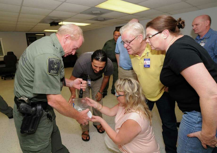 Harris County Precinct 5 Assistant Chief  J.J. Laine, left, shows narcotics to Citizen's Police Academy students Constanin Platon, Karrilyn Ringnald, Jonathon Badger and Lynda Badger during a class designed to increase understanding between officers and local residents. Photo: George Wong / Freelance
