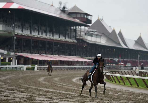 A horse trained by Chad Brown moves across a muddy main track at  Saratoga Race Coruse Wednesday morning, July 1, 2015, in Saratoga Springs, N.Y.  (Skip Dickstein/Times Union) Photo: SKIP DICKSTEIN