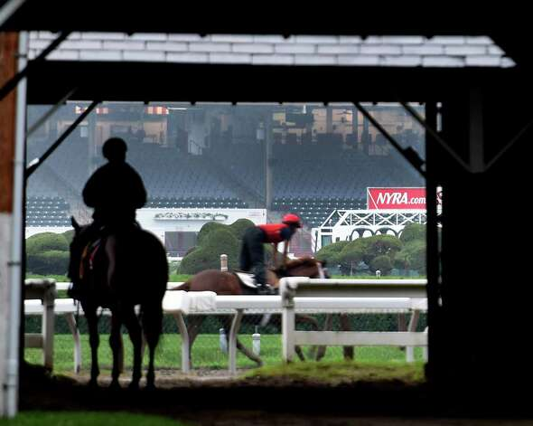 An outrider gets some protection from the rainy weather as horses train on a muddy main track at Saratoga Race Coruse  Wednesday morning, July 1, 2015 in Saratoga Springs, N.Y. (Skip Dickstein/Times Union) Photo: SKIP DICKSTEIN