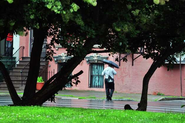 Rain falls on Madison Ave. as a man uses an umbrella to keep dry on Tuesday, June 30, 2015, in Albany, N.Y.    (Paul Buckowski / Times Union)