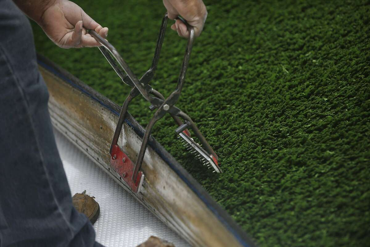 A Field Turf Construction employee uses turf clamps to move the artificial turf into place at the Beach Chalet athletic fields on Tuesday, June 30, 2015 in San Francisco, Calif.