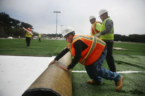Anderson Lee (l to r), Juan Carlos Buenrostro and Ricardo Gonzalez , all with Field Turf Construction, roll out a section of artificial turf at the Beach Chalet athletic fields on Tuesday, June 30, 2015 in San Francisco, Calif.