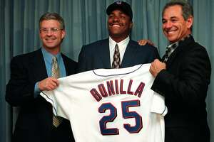 New York Mets general manager Steve Phillips, left, and manager Bobby Valentine hold a jersey in front of their new player Bobby Bonilla in New York Wednesday, Nov. 18, 1998. The Los Angeles Dodgers traded Bonilla to the Mets for reliever Mel Rojas in a deal involving two high-salaried players who were busts last season. (AP Photo/Osamu Honda)
