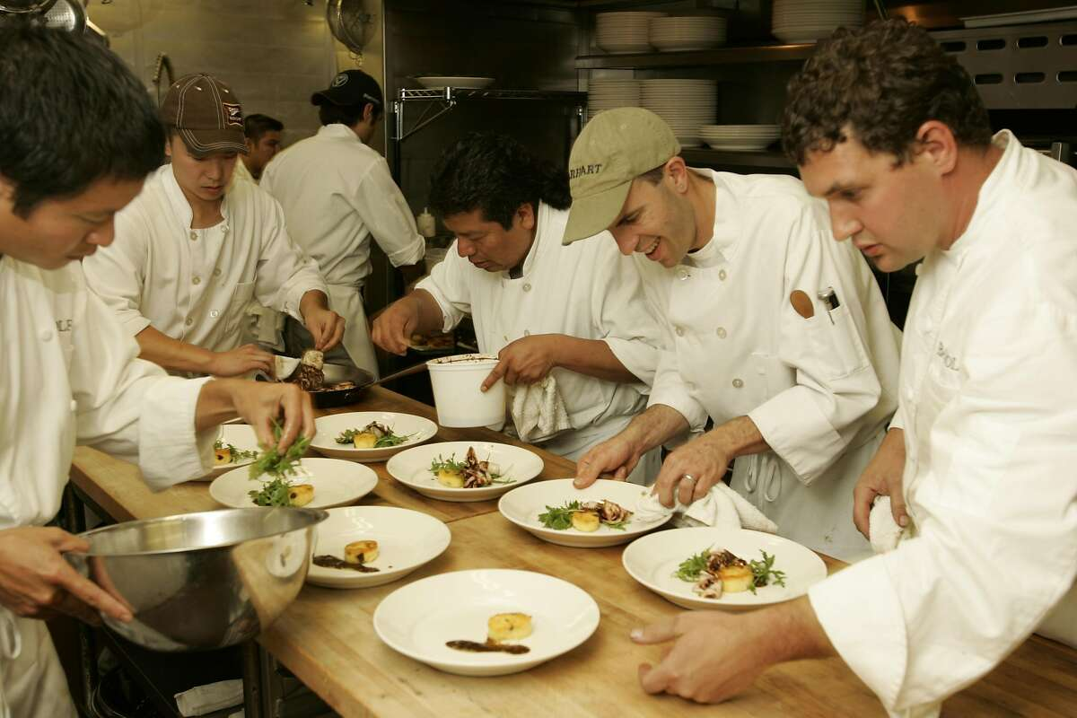 BAYWOLF14_151_cl.JPG Bay Wolf restaurant celebrating its 30th anniversary with a dinner for big-name local food people. The kitchen staff working hard to get the dinner plates out. Chef Louis Le Gassic is at the far right. Event on 9/19/05 in Oakland. Craig Lee / The Chronicle Ran on: 09-21-2005 Chef-owner Michael Wild checks a platter of Bay Wolf's signature roast duck before sending it out to guests at the restaurant's anniversary celebration.