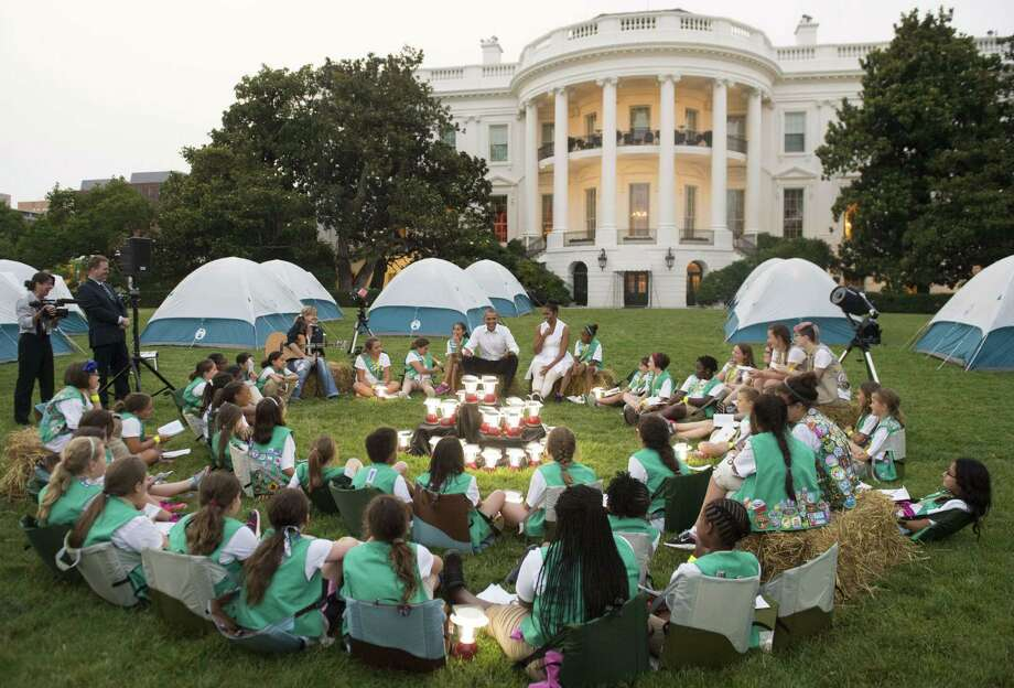 "US President Barack Obama and First Lady Michelle Obama talk with Girl Scouts that are camping overnight on the South Lawn of the White House in Washington, DC, June 30, 2015. Fifty Girl Scouts will spend the night on the White House lawn in camping tents as part of the ""Let's Move"" campaign to fight childhood obesity and increase nutrition awareness. Photo: SAUL LOEB, AFP / Getty Images / AFP"
