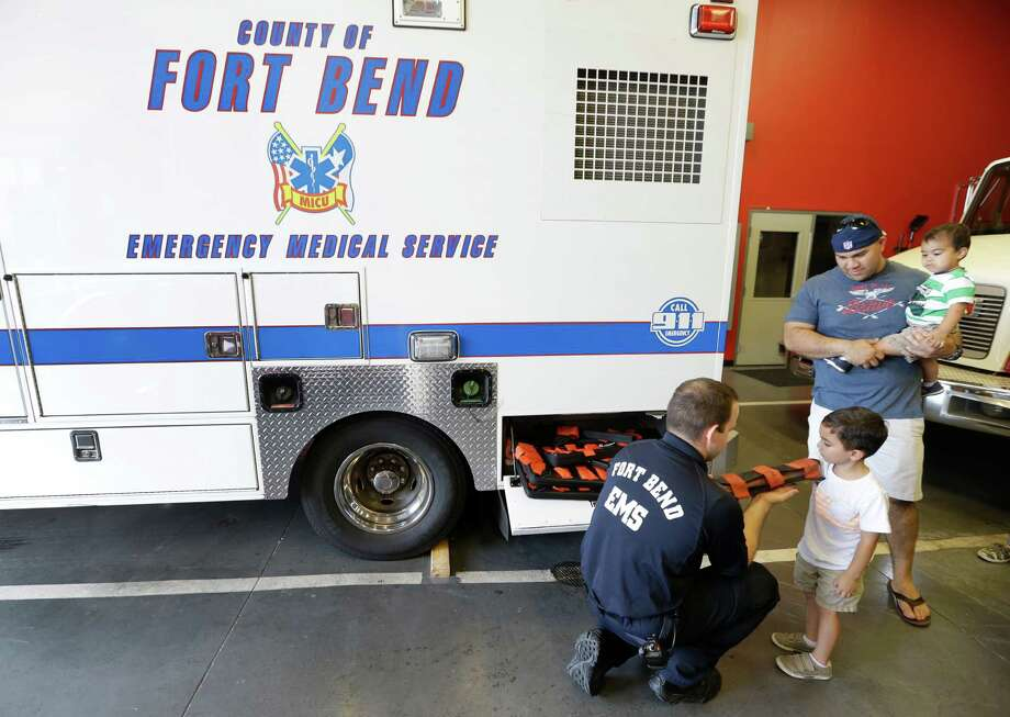 EMT Jose Diaz visits with 4-year-old Phillip Fong III, as his dad, Phillip Fong, holds his brother, Williams Fong, 1, while they tour the Stafford Fire Station No. 3, 11803 Kirkwood Road, Tuesday, June 30, 2015, in Meadows Place. Fort Bend County EMS relocated the Medic 3 ambulance to the fire station in the city of Meadows Place for better response in the growing area. Photo: Melissa Phillip, Houston Chronicle / © 2015  Houston Chronicle