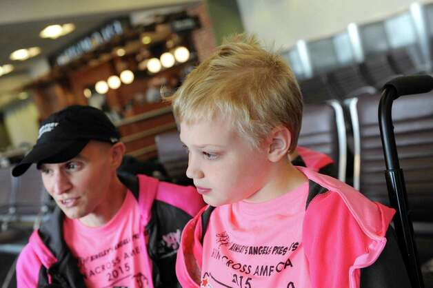 Shamus Evans, 9, right, of Galway and his father, Shaun Evans, talk about their upcoming trek across America on Wednesday, July 1, 2015, at the Albany International Airport in Colonie, N.Y. Shamus, who was born with cerebral palsy, will ride in a running chariot powered by Shaun as his mother, Nichole Evans, and brother, Simon Evans, 7, provide a support vehicle and transport chariots from Ainsley's Angels to donate to others along the way. (Cindy Schultz / Times Union) Photo: Cindy Schultz / 00032457A