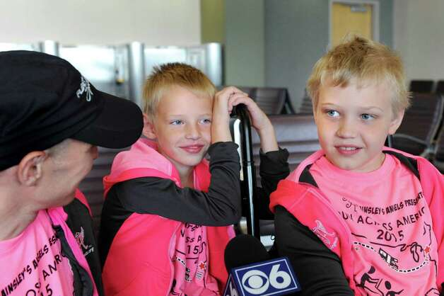 Shamus Evans, 9, right, of Galway, his father, Shaun Evans, left, and brother, Simon Evans, 7, talk about their upcoming trek across America on Wednesday, July 1, 2015, at the Albany International Airport in Colonie, N.Y. Shamus, who was born with cerebral palsy, will ride in a running chariot powered by Shaun as his mother, Nichole Evans, and brother provide a support vehicle and transport chariots from Ainsley's Angels to donate to others along the way. (Cindy Schultz / Times Union) Photo: Cindy Schultz / 00032457A