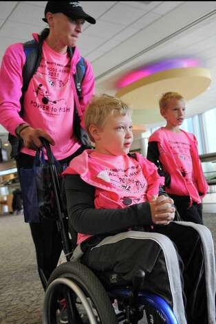 Shamus Evans, 9, center, of Galway, his father, Shaun Evans, left, and brother, Simon Evans, 7, head for the departure gate to fly to Seattle on Wednesday, July 1, 2015, at the Albany International Airport in Colonie, N.Y. Shamus, who was born with cerebral palsy, will ride across America in a running chariot powered by Shaun as his mother, Nichole Evans, and brother provide a support vehicle and transport chariots from Ainsley's Angels to donate to others along the way. (Cindy Schultz / Times Union) Photo: Cindy Schultz / 00032457A