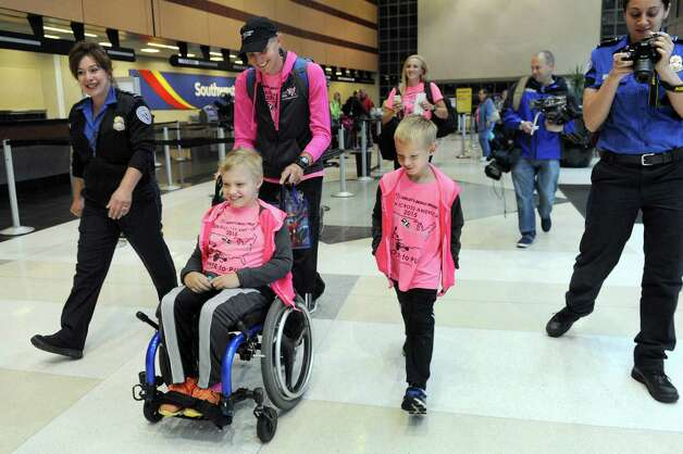 Shamus Evans, 9, second from left, of Galway, his father, Shaun Evans, center, and brother, Simon Evans, 7, are joined by TSA officer Joanne Gigler, left, on Wednesday, July 1, 2015, at the Albany International Airport in Colonie, N.Y. Shamus, who was born with cerebral palsy, will ride from Seattle to New York in a running chariot powered by Shaun as his mother, Nichole Evans, and brother provide a support vehicle and transport chariots from Ainsley's Angels to donate to others along the way. (Cindy Schultz / Times Union) Photo: Cindy Schultz / 00032457A