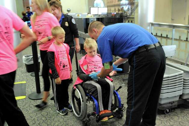 Shamus Evans, 9, center, and brother, Simon Evans, 7, go through airport security on Wednesday, July 1, 2015, at the Albany International Airport in Colonie, N.Y. Shamus, who was born with cerebral palsy, will ride from Seattle to New York in a running chariot powered by his father, Shaun Evans, as his mother, Nichole Evans, and brother provide a support vehicle and transport chariots from Ainsley's Angels to donate to others along the way. (Cindy Schultz / Times Union) Photo: Cindy Schultz / 00032457A