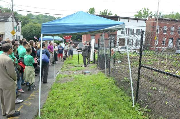 Troy Mayor Lou Rosamilia, center left, and Capital Roots Executive Director Amy Klein, center right, take part in the grand opening of the Capital Roots Ida Street Community Garden on Wednesday, July 1, 2015, in Troy, N.Y.  The  Ida Street Community Garden is the 50th community garden started by Capital Roots.  The garden was created in collaboration with the Troy Little Italy Neighborhood Association and a variety of private individuals and families.    (Paul Buckowski / Times Union) Photo: PAUL BUCKOWSKI / 00032426A