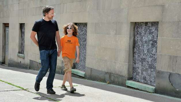 """Artist Thomas Lail and son Coltran Fracalossi-Lial, 10, walk beside his 11 cut xerographic panels """"Crowd"""", at the former St. Anthony's Church along Madison Ave. Wednesday June 24, 2015 in Albany, NY.  (John Carl D'Annibale / Times Union) Photo: John Carl D'Annibale / 00032358A"""