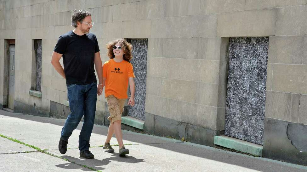 Artist Thomas Lail and son Coltran Fracalossi-Lial, 10, walk beside his 11 cut xerographic panels