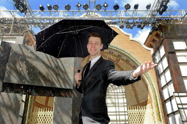 "Rain falls from the set when Andrew Boetcher portrays Gene Kelly's famous role as Don Lockwood in Park Playhouse's ""Singin' in the Rain,"" on Wednesday, June 24, 2015, at Washington Park in Albany, N.Y. (Cindy Schultz / Times Union) Photo: Cindy Schultz / 00032361A"