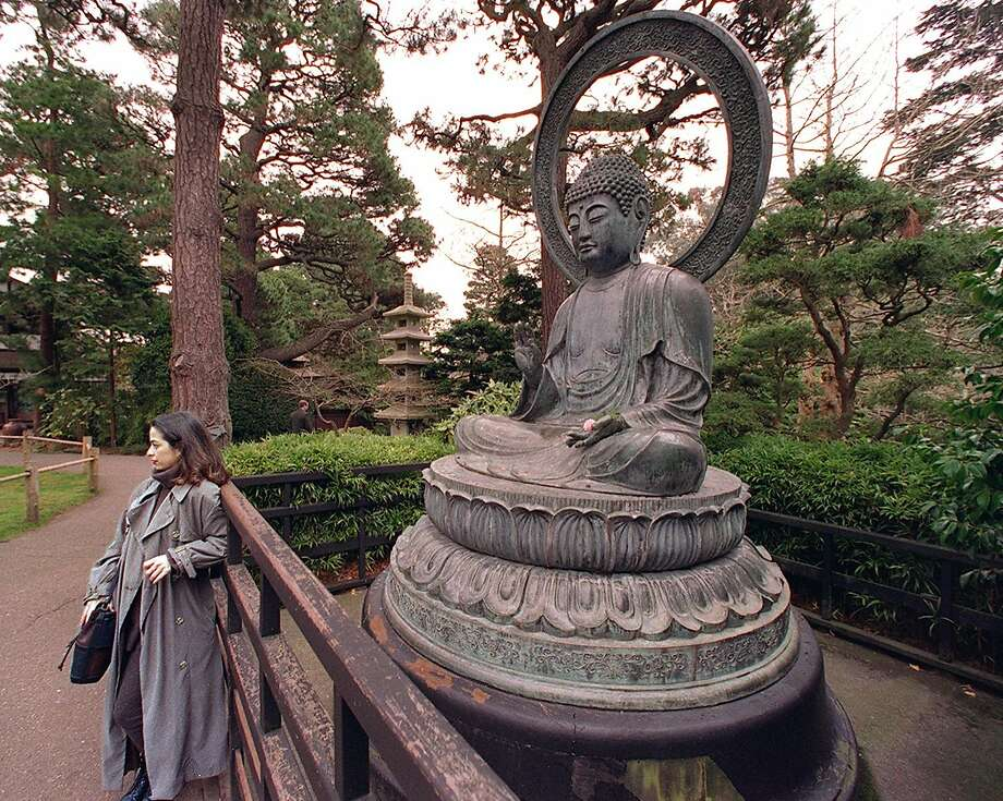 A visitor to the Japanese Tea Garden in Golden Gate Park poses for a souvenir photo in front of the bronze statue of Buddha. Here in 1994, he memorial is in need of nearly $81,000 in repairs. Photo: Chris Stewart, STAFF