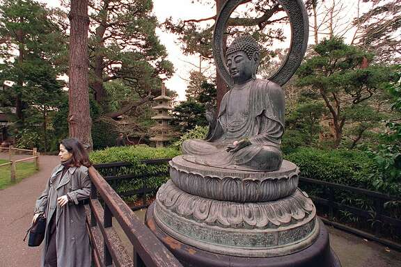MONUMENTS 2/C/20DEC96/CD/CS - A visitor to the Japanese Tea Garden in Golden Gate Park poses for a souvenir photo in front of the bronze statue of Buddha. Cast in Japan 206 years ago, the memorial is in need of nearly $81,000 in repairs.  SAN FRANCISCO CHRONICLE PHOTO BY CHRIS STEWART
