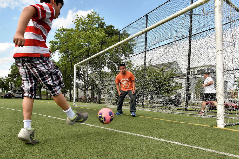Darwin Salazar shoots on his cousin, Kevin Cartagena, during a pick-up game of one-on-one soccer at Lione Park in Stamford, Conn., on Monday, June 29, 2015. Photo: Jason Rearick / Hearst Connecticut Media / Stamford Advocate