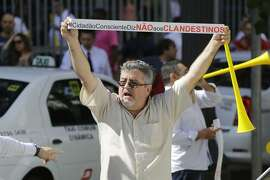 """A taxi driver holds up a sign that reads in Portuguese """"Conscientious citizens say no to illegal drivers"""" to protest Uber outside City Hall in Sao Paulo, Brazil, Tuesday, June 30, 2015. The Sao Paulo city council voted late Tuesday to prohibit the use of smartphone-based ridesharing applications like Uber in the city of 12 million. (AP Photo/Nelson Antoine)"""