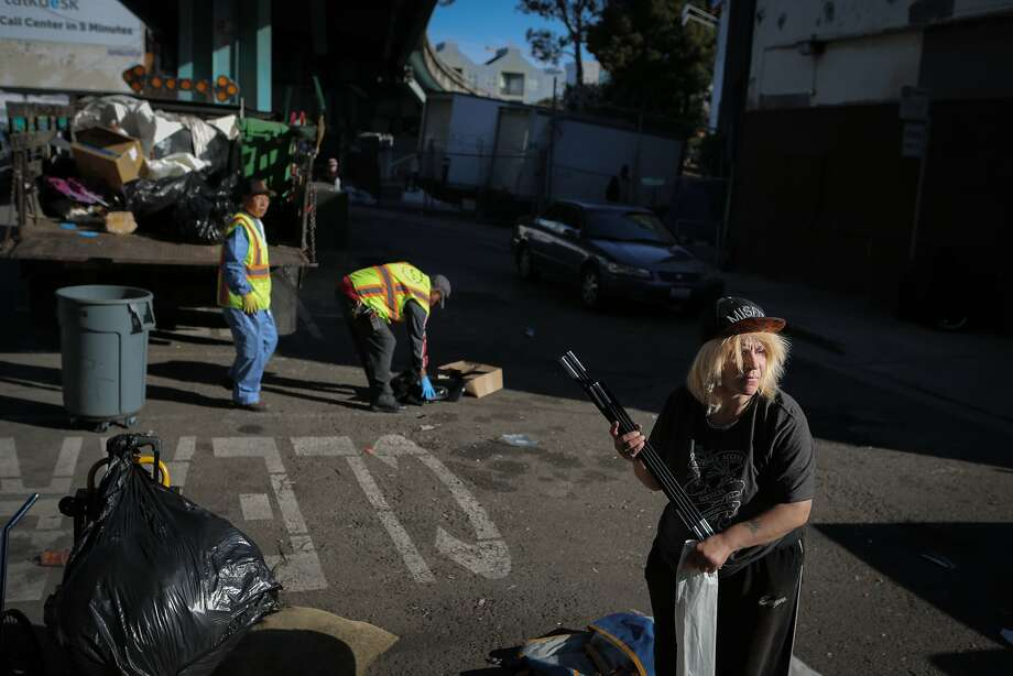 "Jennifer Williams packs up her tent as the San Francisco Public Works Department's ""alley crew"" begins cleaning the homeless encampment where she lives at Dore Alley in San Francisco, California, on Wednesday, July 1, 2015. The alley crew visits homeless encampments on a daily basis to disinfect the ground and haul away refuse. Williams says she has struggled with homelessness since the day she quit prostitution 15 years ago. She is HIV positive and wants more than anything to get help from the Navigation Center, a local homeless shelter, but says she hasn't been taken in after a year of trying. Photo: Loren Elliott, The Chronicle"