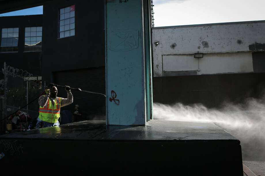 "Bernard Sices, an employee of the San Francisco Public Works Department's ""alley crew"", power washes the sidewalk at a homeless encampment at Dore Alley in San Francisco, California, on Wednesday, July 1, 2015. The alley crew visits homeless encampments on a daily basis to disinfect the ground and haul away refuse. Photo: Loren Elliott, The Chronicle"