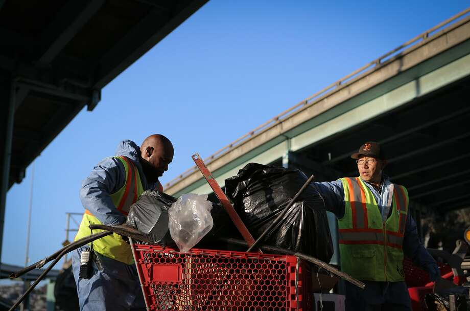 "Bernard Sices (left) and Yu Chun Jin, employees of the San Francisco Public Works Department's ""alley crew"", round up debris to be hauled away from a homeless encampment at 8th and Brannan Streets in San Francisco, California, on Wednesday, July 1, 2015. The alley crew visits homeless encampments on a daily basis to disinfect the ground and haul away refuse. Photo: Loren Elliott, The Chronicle"