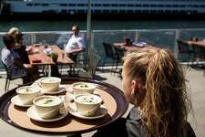 On the outside deck, customers are served on the revamped Seattle waterfront restaurant, Ivar?•s Acres of Clams and Fish Bar, photographed Wednesday, July 1, 2015, in Seattle, Washington. The 20 million dollar transformation includes an overhauled interior, state-of-the-art kitchen, additional seating and an outdoor patio offering views of the Puget Sound and Olympic Mountains.