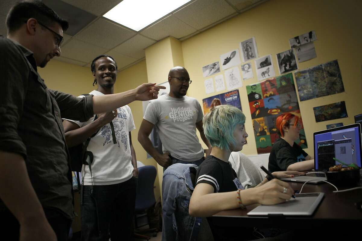 Brendan Milos (left), Ty Moore (middle), and Jason Young (right) check in on some animation and illustration work at MindBlown Labs in Oakland, California, on Wednesday, July 1, 2015.
