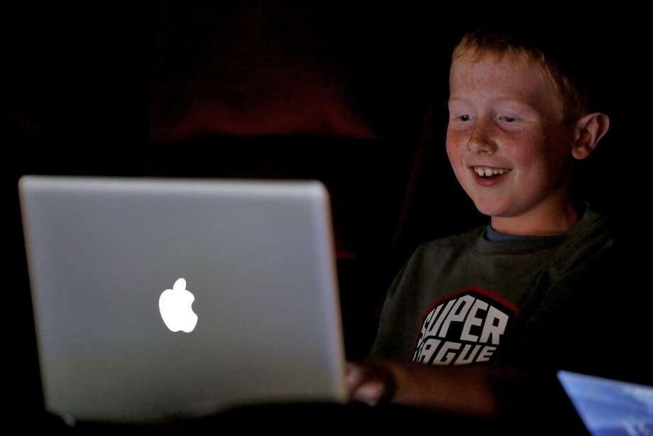 Matthew Bowers smiles during a game of Minecraft in a movie theater in Redwood City, California, on Tuesday, June 23, 2015. The event was put on by Super League Gaming as a demo of a league they want to launch in September. Photo: Connor Radnovich, The Chronicle