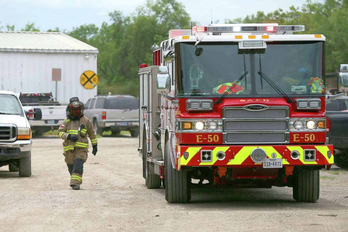 A firerighter with netting over his head leaves the scene Wednesday afternoon July 1, 2015 of a bee attack at a business in the 10700 block of S. Zarzamora Street that sent three people to the hospital., including an 84-year-old man who was in critical condition after he attempted to hide in his car when the attack started but was unable to get the windows rolled up.