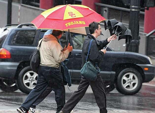Men use umbrellas as they cross State St. in the rain on Wednesday, July 1, 2015 in Albany, N.Y. (Lori Van Buren / Times Union) Photo: Lori Van Buren