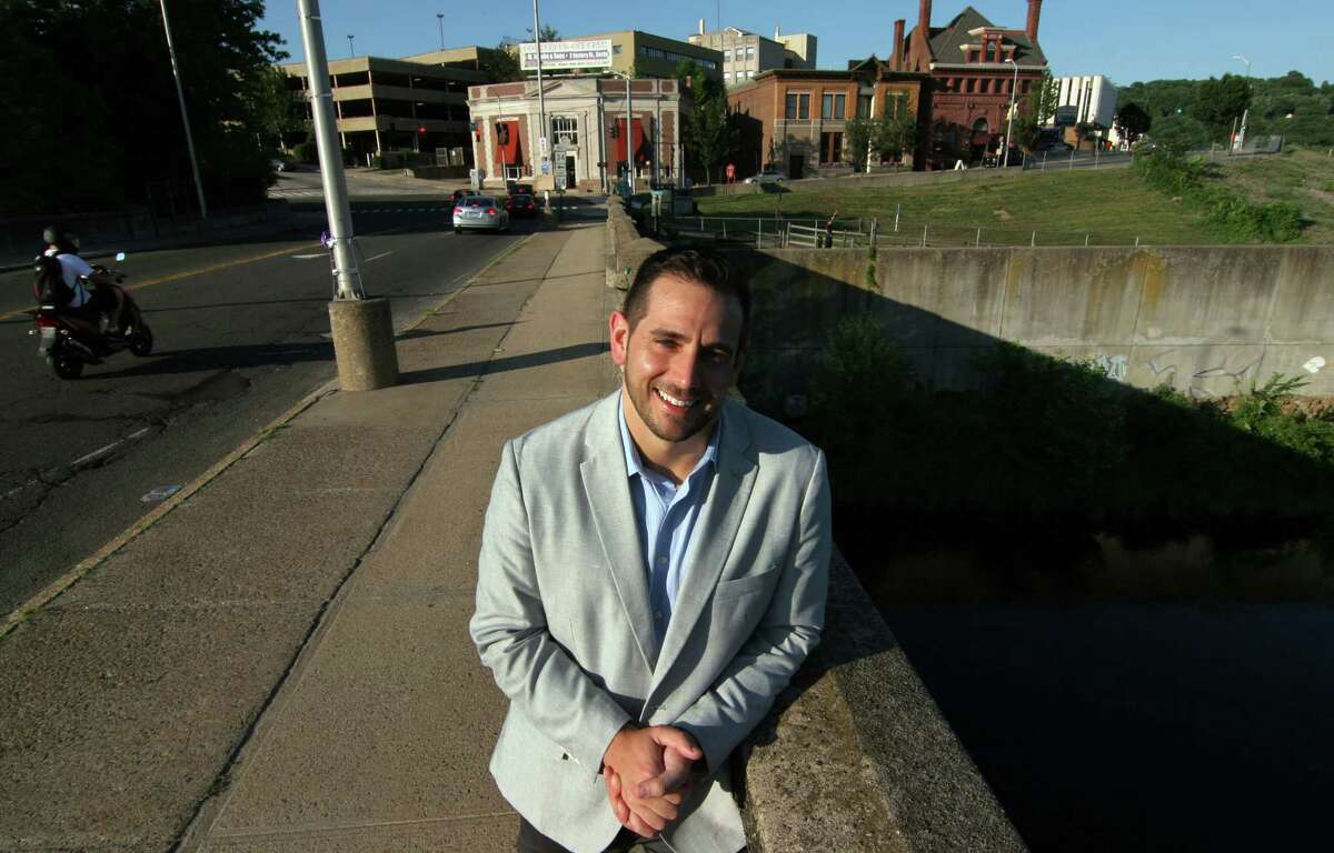 Derby native J.R. Romano, the newly elected state GOP chairman, poses on Bridge Street with a view of Derby in the background on June 24.