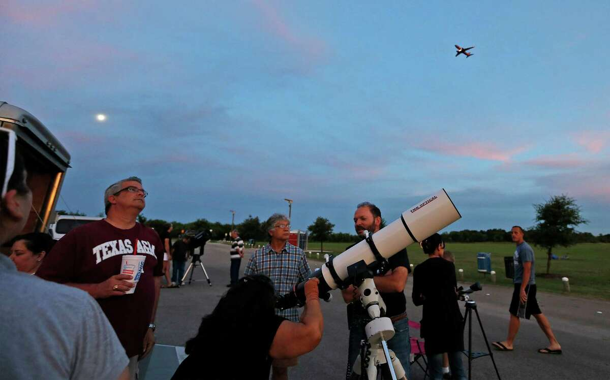 An airliner passes overhead as members of the star-gazing group, San Antonio League of Sidewalk Astronomers (SALSA), hold a star-viewing event at McAllister Park on Tuesday, June 30, 2015. A rare alignment or conjunction of the planets Venus and Jupiter brought out astronomers as well as over 100 curious onlookers to the park toward dusk to get a closer view of the starry heavens. Despite a partially cloudy night which limited the viewing, the local astronomers, some amateur and some professional, provided educational information about the planets as well as the telescopes used to view the night sky. Children and adults lined up to a half dozen telescopes pointed at the sky to catch a glimpse of Venus which was about 48 million miles away and Jupiter which was about 565 million miles away from Earth during last night's conjunction. Though both planets can be seen with the naked eye, the powerful optics on the telescopes allowed people to see the planets with finer precision and clarity. Astronomers say this alignment of planets may have also occurred around 2 and 3 B.C. and may be what many call the Star of Bethlehem or the Christmas star. SALSA founding member, Bryan Tobias, relishes the meetings and viewing parties. When the group meets on Wednesdays of each week and bring out their various telescopes, the group attracts onlookers.