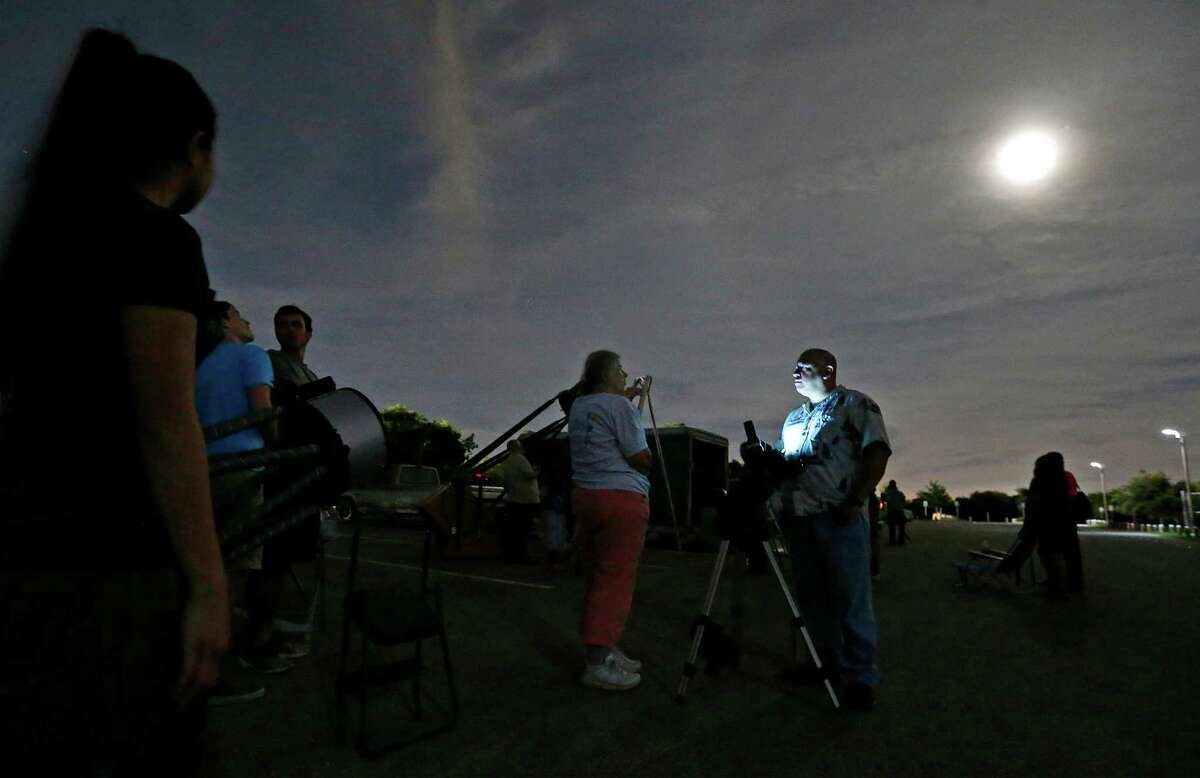 Astronomer Rene Cardenas (illuminated by light) chats with Carolyn Atkins as members of the star-gazing group, San Antonio League of Sidewalk Astronomers (SALSA), hold a star-viewing event at McAllister Park on Tuesday, June 30, 2015. A rare alignment or conjunction of the planets Venus and Jupiter brought out astronomers as well as over 100 curious onlookers to the park toward dusk to get a closer view of the starry heavens. Despite a partially cloudy night which limited the viewing, the local astronomers, some amateur and some professional, provided educational information about the planets as well as the telescopes used to view the night sky. Children and adults lined up to a half dozen telescopes pointed at the sky to catch a glimpse of Venus which was about 48 million miles away and Jupiter which was about 565 million miles away from Earth during last night's conjunction. Though both planets can be seen with the naked eye, the powerful optics on the telescopes allowed people to see the planets with finer precision and clarity. Astronomers say this alignment of planets may have also occurred around 2 and 3 B.C. and may be what many call the Star of Bethlehem or the Christmas star. SALSA founding member, Bryan Tobias, relishes the meetings and viewing parties. When the group meets on Wednesdays of each week and bring out their various telescopes, the group attracts onlookers.