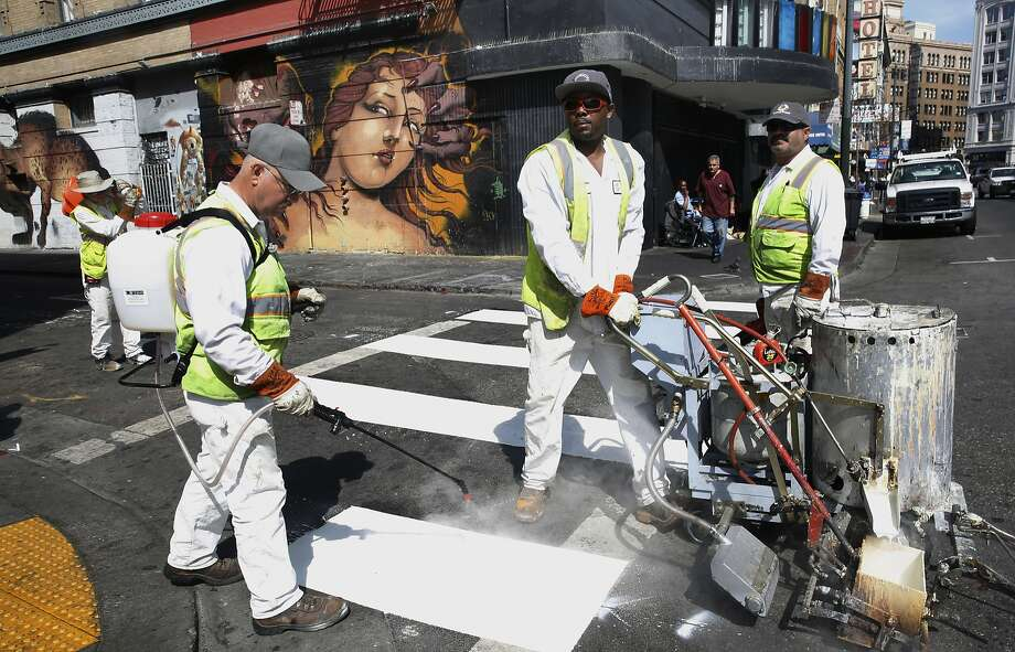 San Francisco Municipal Transportation agency employees paint more lines to pedestrian walks on Sixth at Stevenson streets in San Francisco. Photo: Liz Hafalia, The Chronicle