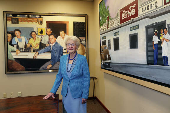 Rosemary Kowalski poses by paintings by Jesse Treviño artwork at the RK Group offices at 1220 East Commerce.