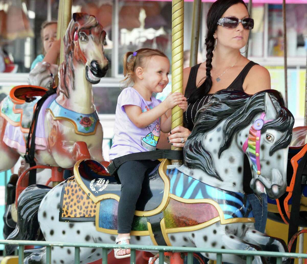 Three-year-old Gabriella Merriman rides the Merry Go Round with her mother Nicole Merriman of Rotterdam at the Grand opening of Huck Finn's Playland Wednesday July 1, 2015, Albany, NY. (John Carl D'Annibale / Times Union)