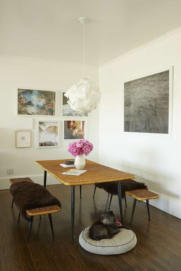 The dining room of Thayer Allyson Gowdy's Bernal Heights home in S.F. exhibits her penchant for texture, with sheepskins topping the rattan benches that pair with the rattan table from Stuff. Art on the walls includes works by friends. Photo: Thayer Allyson Gowdy