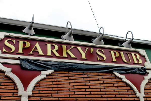 Old school light fixtures illuminate the Sparky's Pub hanging on the bar's classic brick wall.
