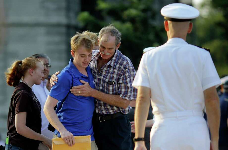 "Jim Johnston, center, of Chapel Hill, N.C., embraces his son, prospective plebe Dan Johnston, before watching him enter Induction Day at the U.S. Naval Academy, Wednesday, July 1, 2015, in Annapolis, Md. More than 1,100 young men and women reported for ""I-Day,"" where they received haircuts, medical examinations, new uniforms and instructions on how to salute and address superiors before taking an oath of office to become members of academy's newest class.  Photo: Patrick Semansky, Associated Press / AP"
