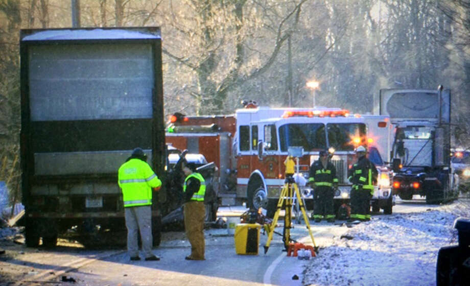 Crews investigate the scene of a double fatal crash involving a 12-ton semitrailer in Ohio. Seventeen months later, federal regulators are questioning whether a defective trailer hitch may be at fault. Photo: Glenn Hartong /The Enquirer / The Cincinnati Enquirer