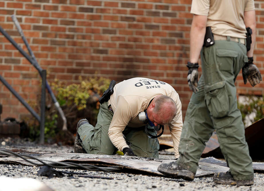 A state investigator examines the charred remains of a door outside Mount Zion African Methodist Episcopal church. Photo: Veasey Conway /Associated Press / Florence Morning News